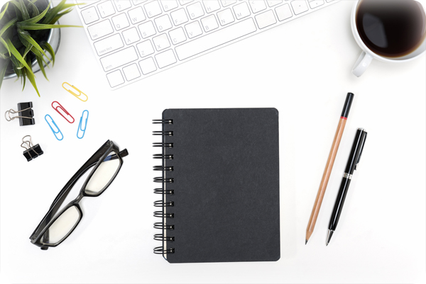 Black notebook with eye glasses, pen, pencil, computer desktop, cup of coffee and small flower plant on white desk table background with copy space, flat lay top view